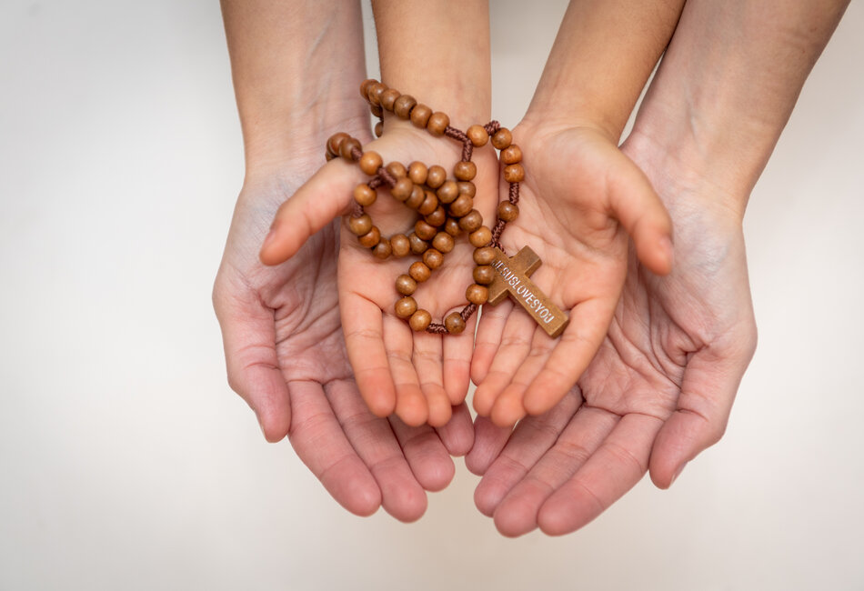 Adult and child hands holding rosary beads